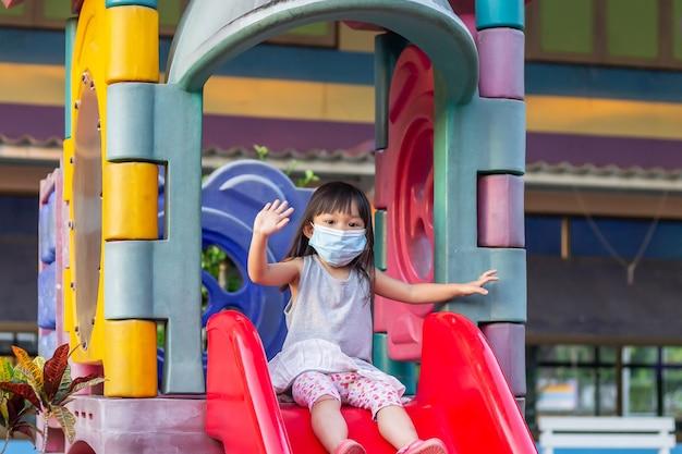 행복 한 아시아 아이 소녀 웃 고 패브릭 마스크를 쓰고. 그녀는 놀이터에서 슬라이더 바 장난감을 가지고 놀고,