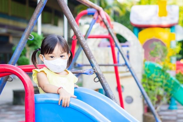 Счастливая азиатская девушка ребенка усмехаясь и нося маску ткани.