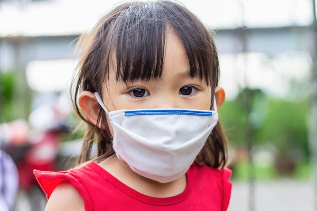 Happy asian child girl smiling and wearing fabric mask