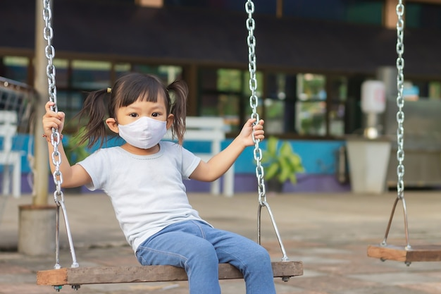 그녀는 공원 놀이터에서 스윙 좌석 장난감을 재생할 때 패브릭 얼굴 마스크를 쓰고 행복 아시아 아이 소녀.