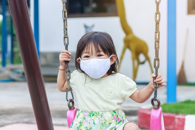 패브릭 마스크를 쓰고 행복 한 아시아 아이 소녀. 그녀는 놀이터에서 놀고 있습니다.
