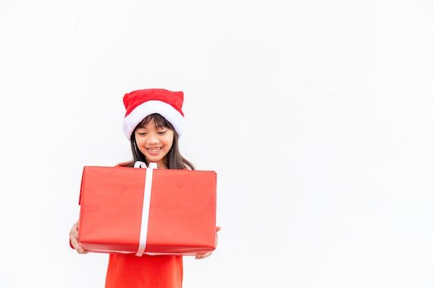 크리스마스 선물을 들고 산타 빨간 모자에 행복 한 아시아 아이. 크리스마스 time.on 흰색 배경입니다.