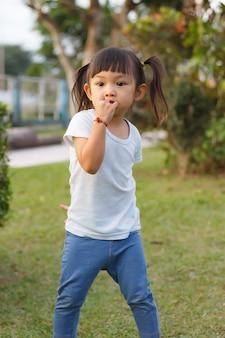 공원 놀이터에서 노는 행복 한 아시아 아이. 그녀는 입에 손가락을 빨고있다. 학습 및 아이 개념. 패션. 세로