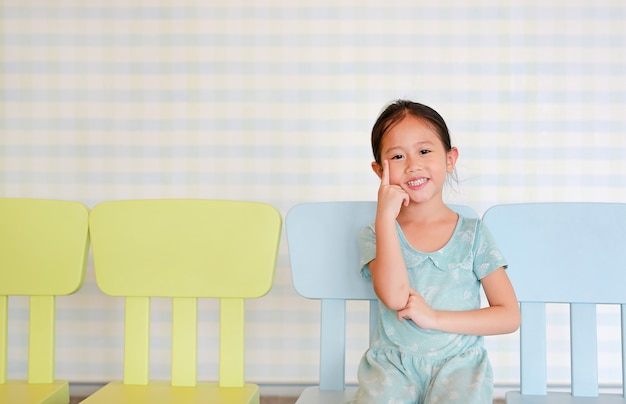 Happy asian child preschool girl in a kindergarten room poses on plastic baby chair.
