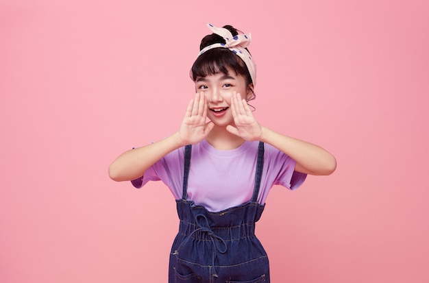 Happy asian child shout story or making announcement isolated on pink wall.