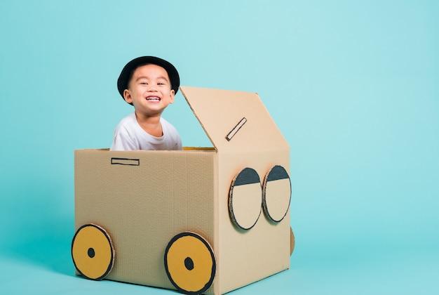 행복한 아시아 어린이 소년은 판지 상자 상상으로 창의적인 놀이 자동차를 운전하면서 미소를 짓습니다.