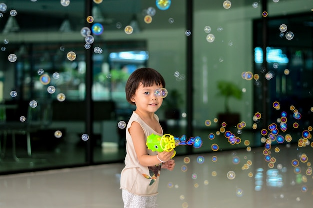Happy asian children girl playing with soap bubbles.