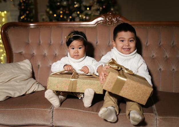 家の木のそばのソファに座って、開いて笑って、贈り物を与える幸せなアジアの子供たち
