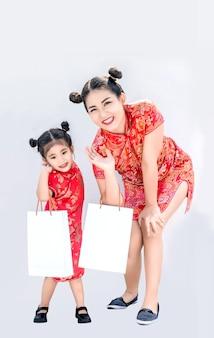 행복 한 아시아 중국 어머니와 daugther islated 배경에 중국 신년 축제에서 치파오 드레스와 함께 쇼핑