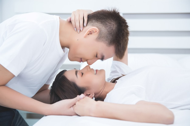 Happy asian couple on the bed at home