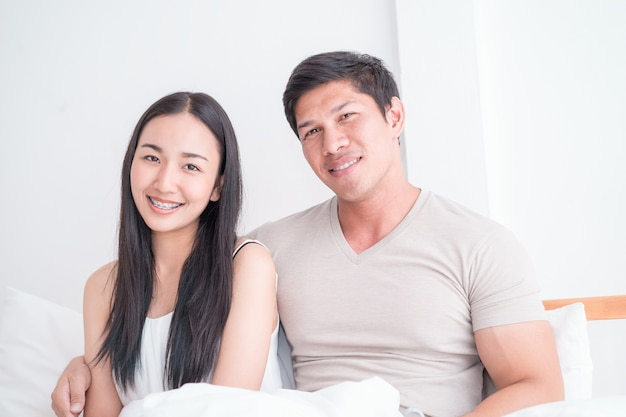 Happy asian couple on bed with bright morning light