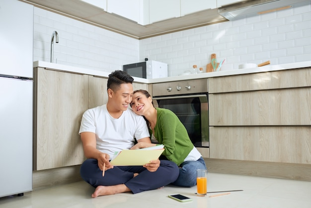 Happy asian couple blueprint moving to new home