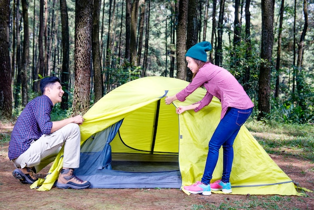 Happy asian couple build-up tent together