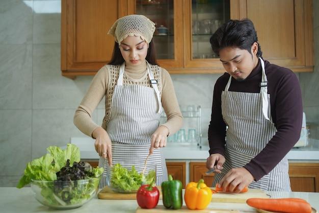 함께 요리하는 행복 한 아시아 커플. 남편과 아내가 집에서 부엌에서 건강한 야채 음식을 준비합니다.