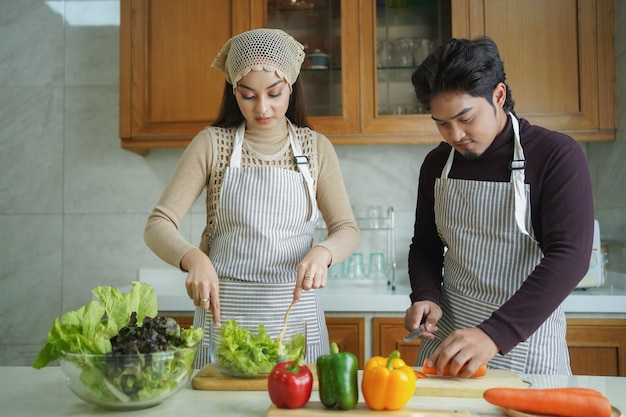 Happy asian couple cooking together. husband and wife in their kitchen at home preparing healthy vegetable food.