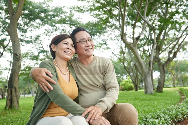 Happy asian couple on date sitting on bench in park looking away