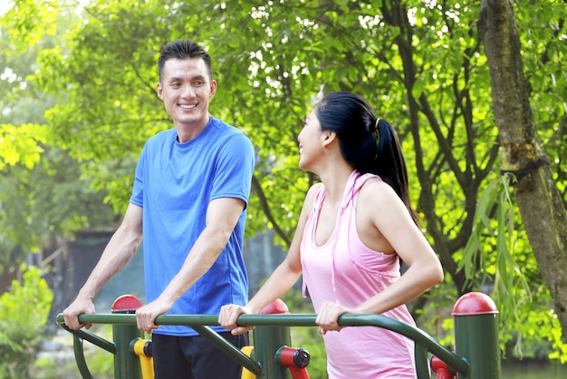 Happy asian couple doing workout while talking