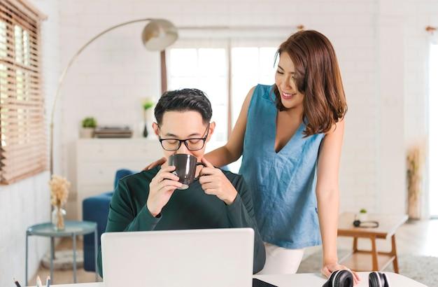 ホームオフィスのデスクトップコンピュータでコーヒーを飲む幸せなアジアのカップル。