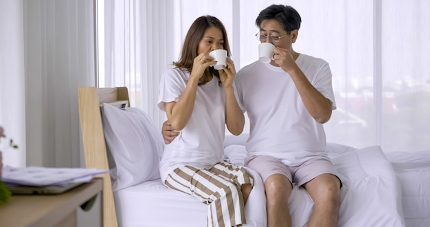 Happy asian couple drinking coffee together in bedroom.