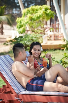 Happy asian couple enjoying cocktails outdoors on sun loungers