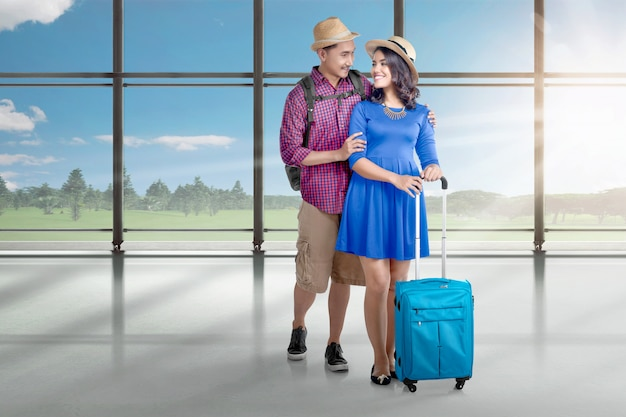 Happy asian couple going to traveling with plane