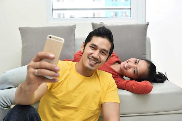 Happy asian couple having fun and taking a selfie