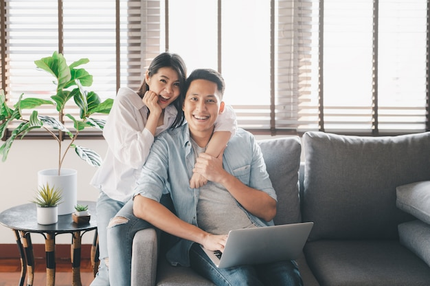 Happy asian couple having a good time at home