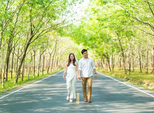 Счастливая азиатская влюбленная пара на дороге с аркой дерева
