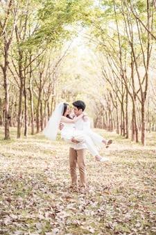 나무 아치와 사랑에 행복 한 아시아 부부