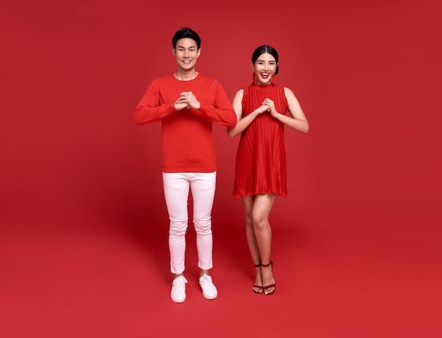 밝은 빨간색 배경에 새 해 복 많이 받으세요 2021 인사말 축 하의 제스처와 함께 빨간색 캐주얼 복장에 행복 한 아시아 부부.