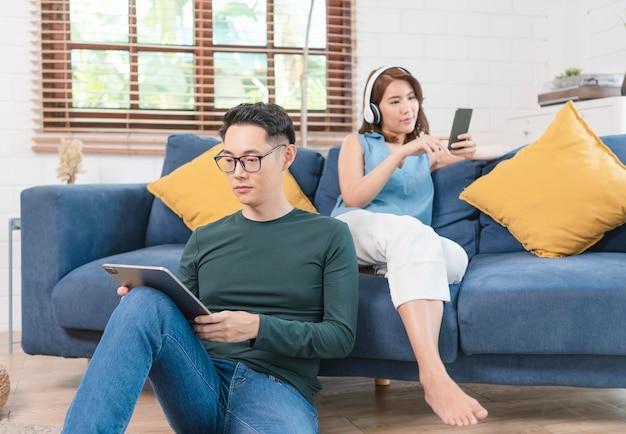 Felice coppia asiatica sta trascorrendo il fine settimana insieme sul divano in casa, rilassandosi e godendosi la navigazione in internet.