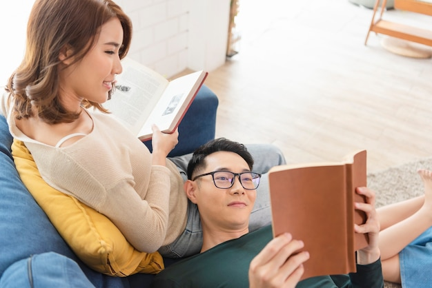 Happy asian couple is spending weekend together on couch indoors at home, relaxing and enjoying reading book.