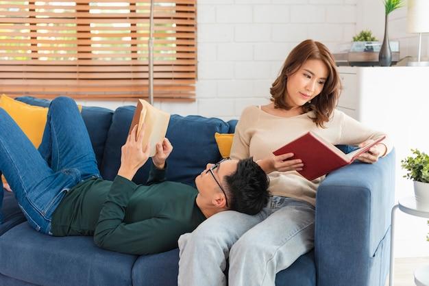 幸せなアジアのカップルは、自宅の屋内のソファで週末を一緒に過ごし、リラックスして本を読んで楽しんでいます。