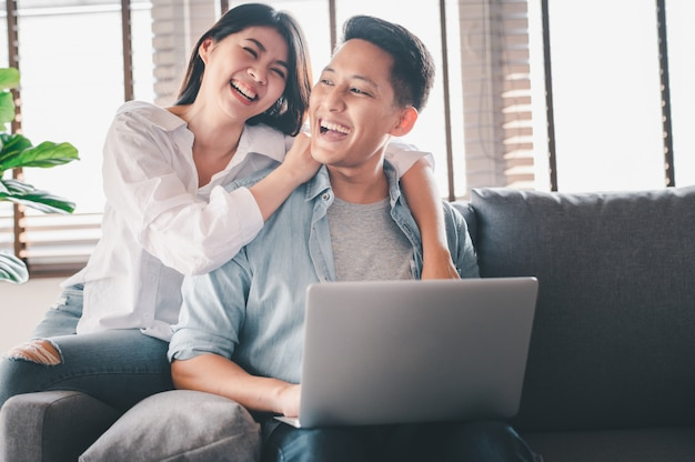 Happy asian couple in love laughing while using laptop