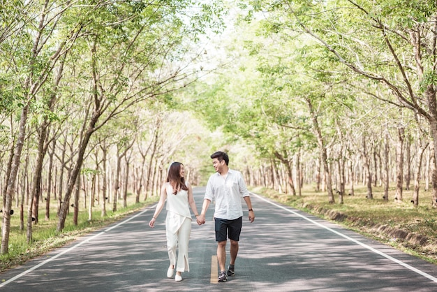 Happy asian couple in love on road with tree arch