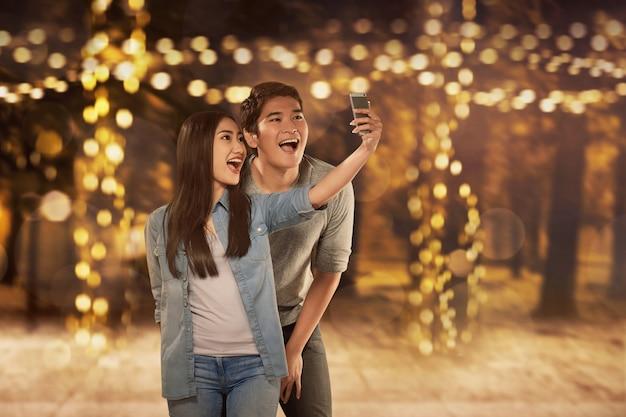 Happy asian couple in love taking selfie photo