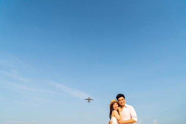 Happy asian couple in love with blue sky