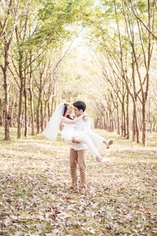 Happy asian couple in love with tree arch