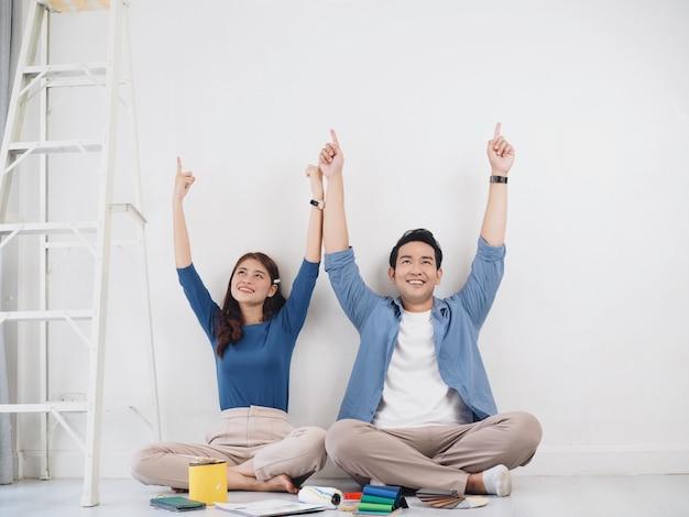 Счастливая азиатская пара любитель роспись стены в новом доме вместе