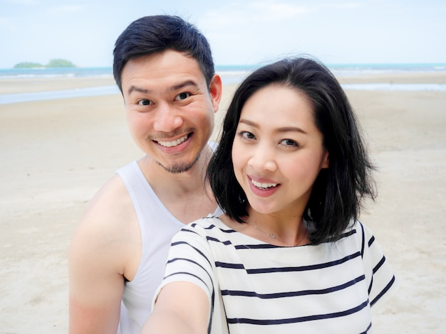 Happy asian couple lover on summer beach vacation.