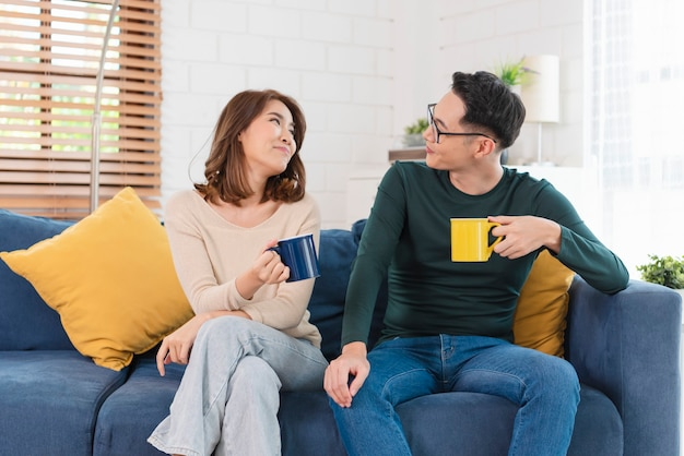 Happy asian couple man and woman is spending weekend together on couch indoors at home, relaxing and enjoying drinking coffee.