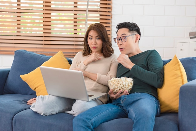 Happy asian couple man and woman is spending weekend together watching movie on couch indoors at home, relaxing and enjoying eating popcorn.