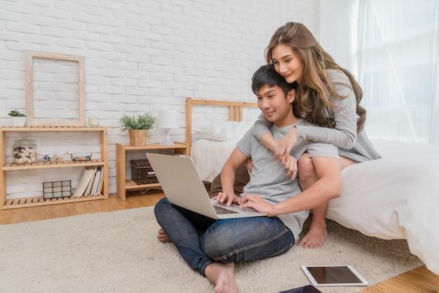 Счастливая азиатская пара, планирование и бронирование отеля для путешествия с технологическим ноутбуком