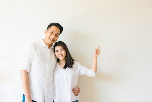 Happy asian couple pointing finger at empty copy space on the wall