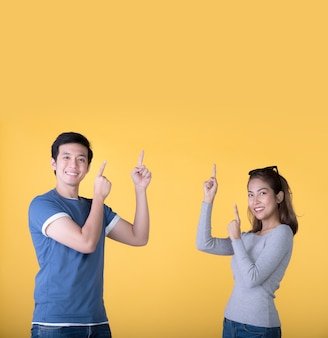 노란색 배경 위에 텍스트를 위한 빈 복사 공간에서 손가락을 가리키는 행복한 아시아 커플