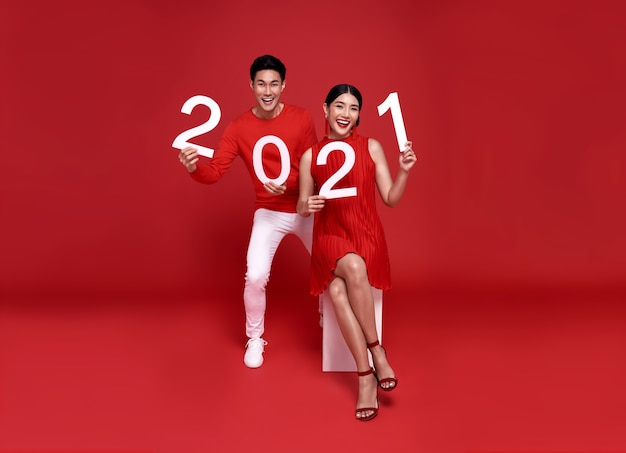 Happy asian couple in red casual attire showing number 2021 greeting happy new year with smiles on bright red.