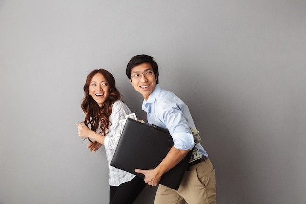 Happy asian couple running away isolated, holding briefcase full of money banknotes