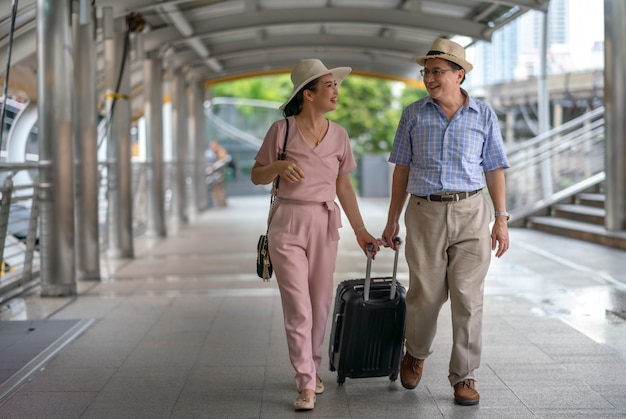 Happy asian couple senior tourists holding suitcase handle in the city while traveling