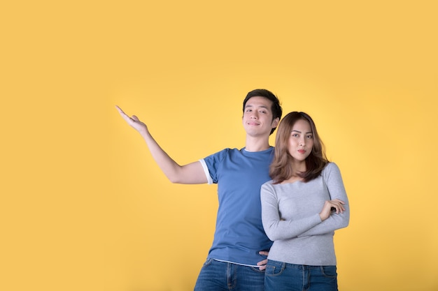 행복한 아시아 커플은 비즈니스에서 복사 공간을 보여주고 제시하고 노란색 배경에서 카메라를 보고 있습니다.