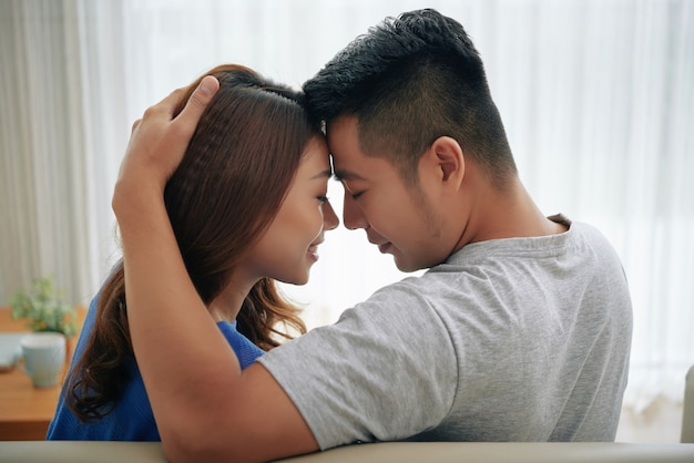Happy asian couple sitting on couch at home and embracing, touching foreheads